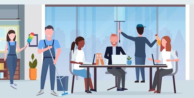 Conserjes equipo de limpieza en uniforme trabajando junto con equipo profesional concepto de servicio de limpieza centro de trabajo creativo centro de oficina moderno interior plano horizontal