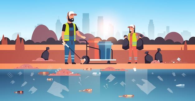 Conserjes recolectando basura y empacando en bolsas negras limpiadores pareja trabajando juntos en el área de playa servicio de limpieza concepto de mejora ambiental horizontal de la orilla del río horizontal de fondo
