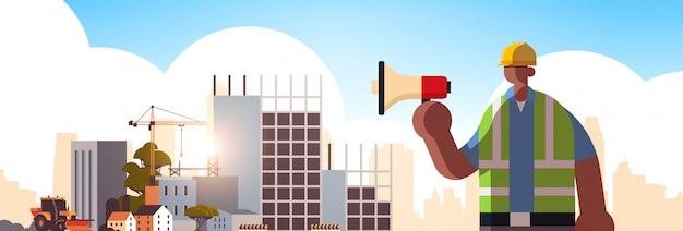 Constructor masculino con megáfono trabajador ocupado usando altavoz haciendo anuncio trabajador industrial en concepto de construcción uniforme construcción sitio fondo plano retrato horizontal