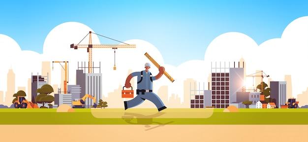 Constructor de sexo masculino que lleva la caja de herramientas y el carpintero nivel afroamericano trabajador ocupado ejecutando pose edificio concepto construcción sitio plano horizontal de longitud completa