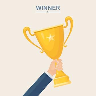 Copa de trofeo en mano. copa de oro sobre fondo blanco. premios al ganador, campeón. concepto de victoria, premio, campeonato, liderazgo, logro.
