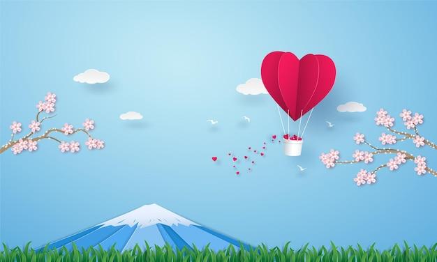 Corazón de globo de aire caliente de origami volando en el cielo sobre la hierba con la montaña fuji y flor de cerezo.