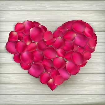Corazón de pétalos de rosa sobre tablas de madera. archivo incluido