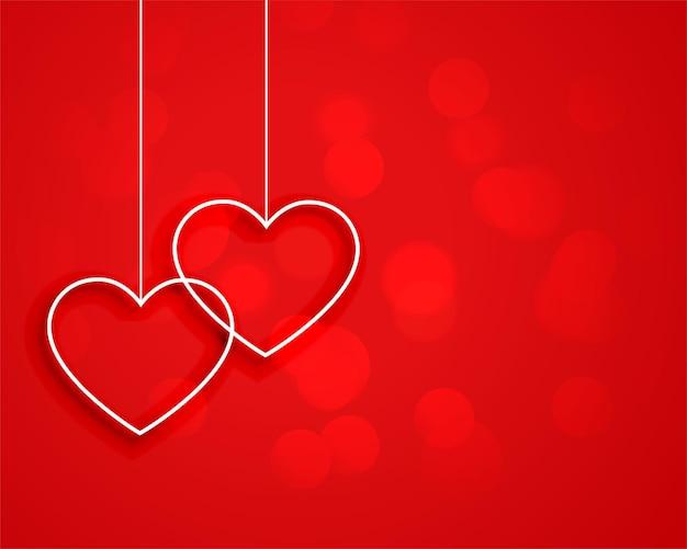 Corazones colgantes de estilo minimalista sobre fondo rojo