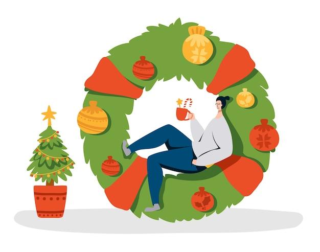 Corona de navidad, árbol y hombre pequeño con taza de café caliente en enorme corona verde