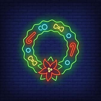 Corona de navidad con flor de pascua, bastones de caramelo, letrero de neón