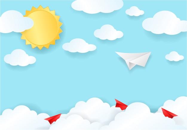 Corte de papel de avión blanco y rojo sobre cielo azul con nubes y luz solar