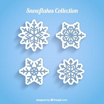 Cuatro copos de nieve blancos sobre un fondo azul
