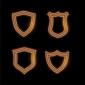 Cuatro iconos de escudo de neón dorado
