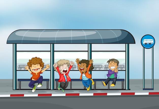 Cuatro niños felices en el cobertizo de espera
