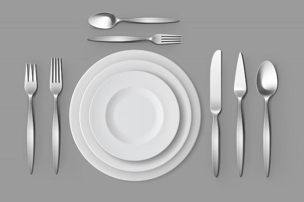 Cubiertos tenedores de plata cucharas y cuchillos con platos ajuste de mesa