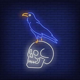 Cuervo sentado en letrero de neón de cráneo humano