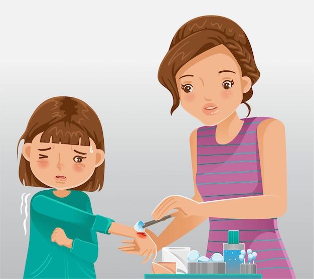 Cuidador infantil. niña llorando de dolor lastimándose la mano. mather proporciona primeros auxilios.