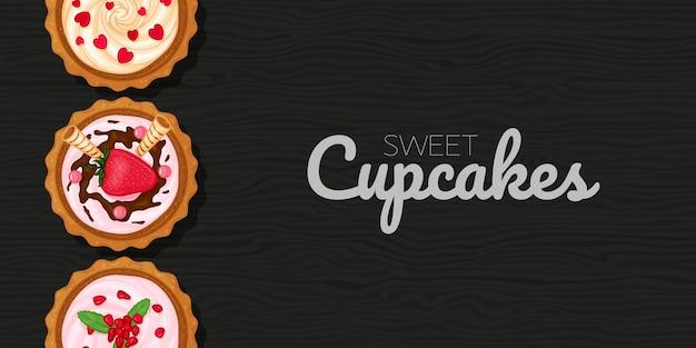 Cupcakes dulces sobre fondo negro madera