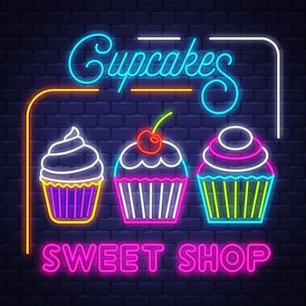 Cupcakes shop- vector de señal de neón. tienda de magdalenas - letrero de neón sobre fondo de pared de ladrillo
