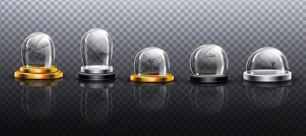 Cúpulas de vidrio roto sobre podio de metal, oro y plata.