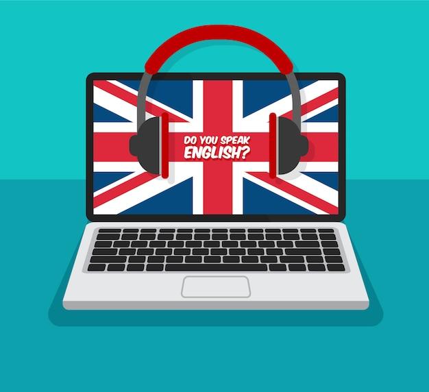 Curso de inglés. aprender en línea. portátil abierto con auriculares y bandera de gran bretaña en una pantalla.