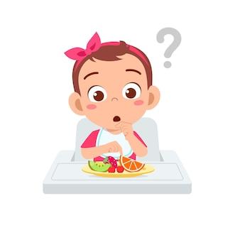 Cute little baby boy comer frutas y verduras