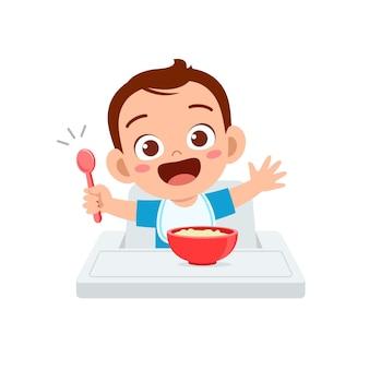 Cute little baby boy comer papilla en un tazón con cuchara