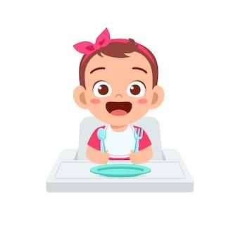Cute little baby girl comer papilla en un tazón con cuchara