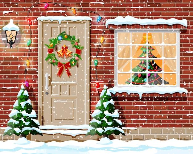 Decoración de fachada navideña con nieve y árboles.
