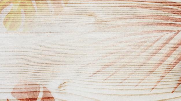 Decoración de hojas sobre fondo de diseño de madera lisa