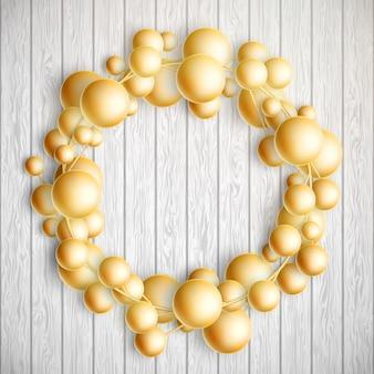 Decoración navideña. guirnalda de bolas de oro sobre fondo blanco de madera. y también incluye