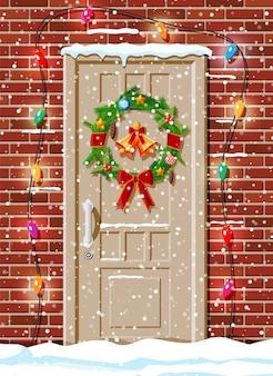 Decoración de puerta navideña con guirnaldas de luces.