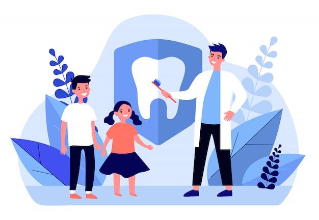 Dentista enseñando a los niños a cepillarse los dientes