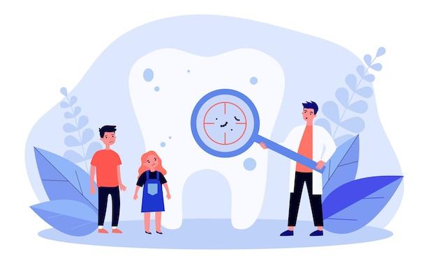 Dentista mostrando caries en los dientes a los niños