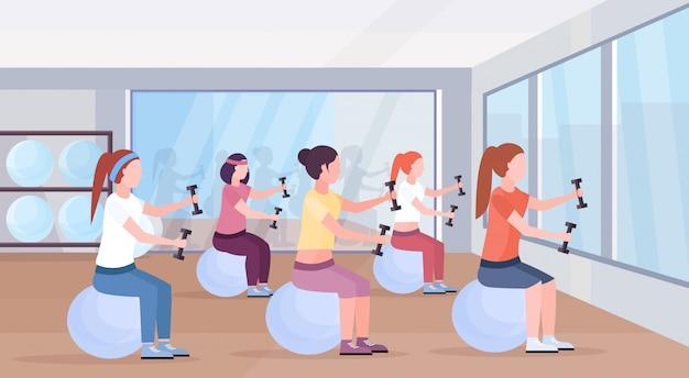 Deportes mujeres grupo sentado fitness bola niñas sosteniendo pesas haciendo ejercicios entrenamiento en gimnasio aeróbico pilates entrenamiento estilo de vida saludable concepto club de salud estudio interior horizontal