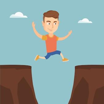 Deportista saltando sobre el acantilado.