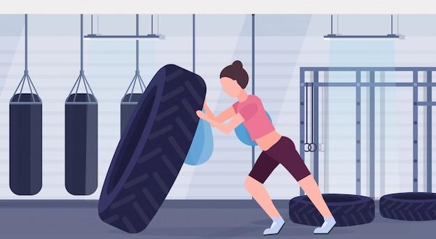 Deportista volteando un neumático haciendo ejercicios duros chica ejercitándose en el gimnasio con sacos de boxeo entrenamiento crossfit concepto de estilo de vida saludable moderno club de salud interior horizontal