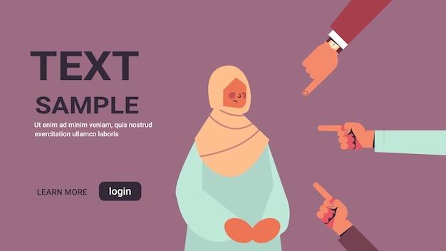 Deprimida niña árabe rodeada de manos dedos burlándose señalando su intimidación desigualdad discriminación racial concepto espacio de copia