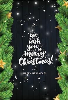 Le deseamos una tarjeta de texto de letras a mano feliz navidad. rama de pino realista con estrellas sobre fondo de madera negra.