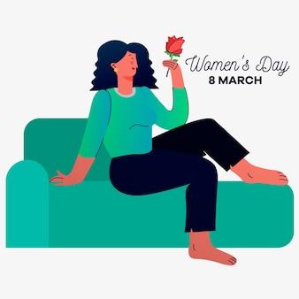 Día de la mujer con mujer en el sofá sosteniendo rosa