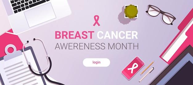 Día mundial del cáncer icono de la cinta rosada concepto de prevención de la conciencia de la enfermedad del seno doctor lugar de trabajo de escritorio con material de oficina vista del ángulo superior copia espacio horizontal