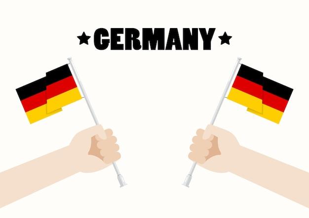 Día nacional de alemania con las manos sosteniendo banderas de alemania