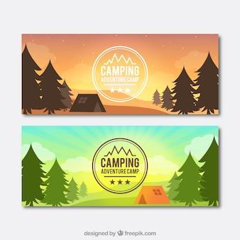 El día y la puesta de sol paisaje con un banners de la tienda de campaña