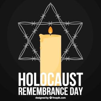 Día del recuerdo del holocausto, una vela y una estrella sobre un fondo negro