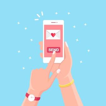 Día de san valentín . envíe o reciba amor sms, carta, correo electrónico con teléfono móvil blanco. asimiento de la mano humana teléfono móvil, smartphone en el fondo. sobre con corazón rojo.