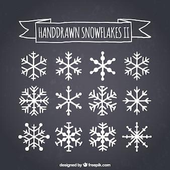 Dibujado a mano los copos de nieve en la pizarra