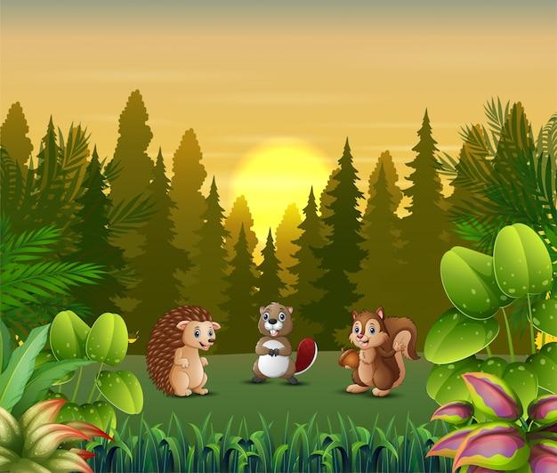 Dibujos animados de animales jugando en el paisaje al atardecer