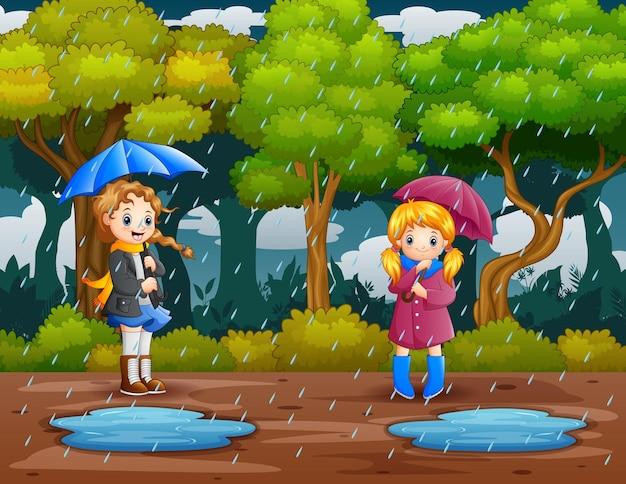 Dibujos animados de dos niñas con paraguas bajo la lluvia en el bosque