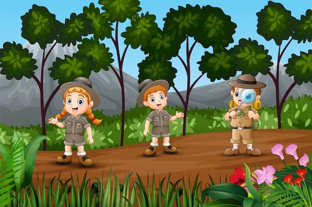 Dibujos animados a niños explorando en el bosque
