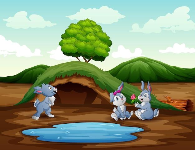 Dibujos animados de tres conejos jugando cerca del pequeño estanque