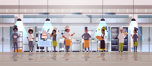 Diferentes chefs de pie juntos afroamericanos hombres mujeres r en uniforme de cocina concepto de comida moderna cocina restaurante interior