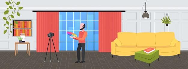 Diseñador de hombre sosteniendo muestras de paleta de colores blogger grabando video en línea con cámara digital en trípode concepto de blogging de red social estudio de diseño moderno interior horizontal completo