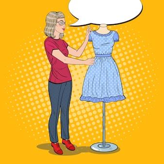 Diseñador de moda femenino sonriente con vestido en un maniquí