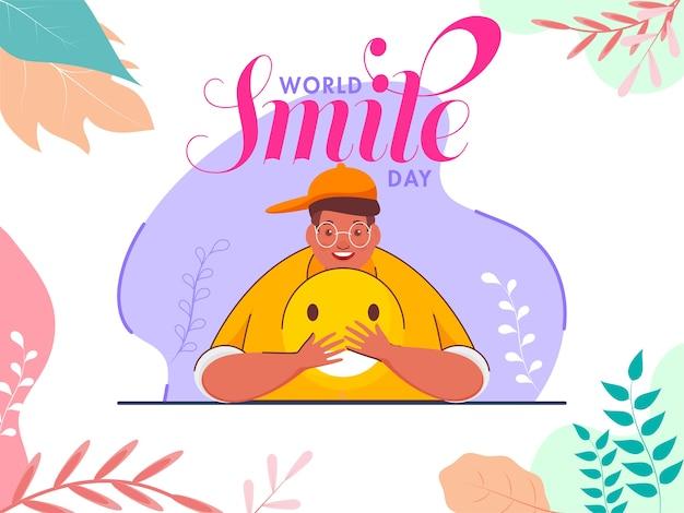 Diseño de carteles del día mundial de la sonrisa con un joven sosteniendo un emoji sonriente y hojas coloridas decoradas sobre fondo blanco.
